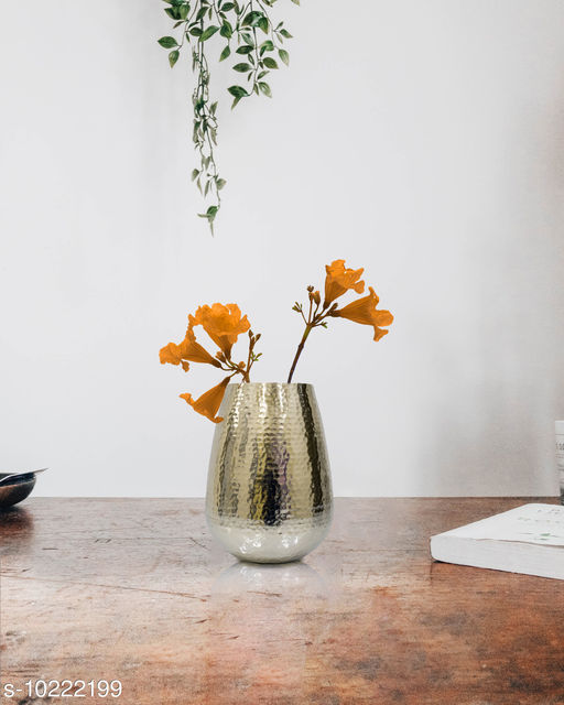 Golden color oval shaped vase in metal with hammered finish